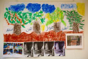 Appelsiini, viikuna, banaani ja oliivi ovat lasten toiveympäristöä, jonka vastakohtana pakolaisleirin tuhottua ympäristöä. Kuva maalauksesta: Kirsti Palonen